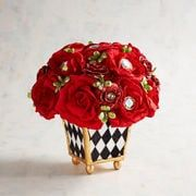 "Irresistible faux red roses blinged out with sparkling ""jewels"" are a Valentine's Day wish come true and will be enjoyed every day of the year. A bold black and white harlequin-print pot is the perfect complement, especially with metallic golden accents."