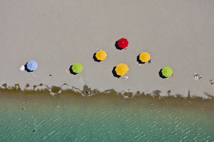 """Bird's Eye View Photography. Parasols. Klaus Leidorf takes aerial photos, mostly in Bavaria, South Germany. He pilots a Cessna 172, taking photos while he steers with his feet. """"For me, the challenge is to capture the combination of the beauty of nature, the graphic aspect and the emotion."""""""