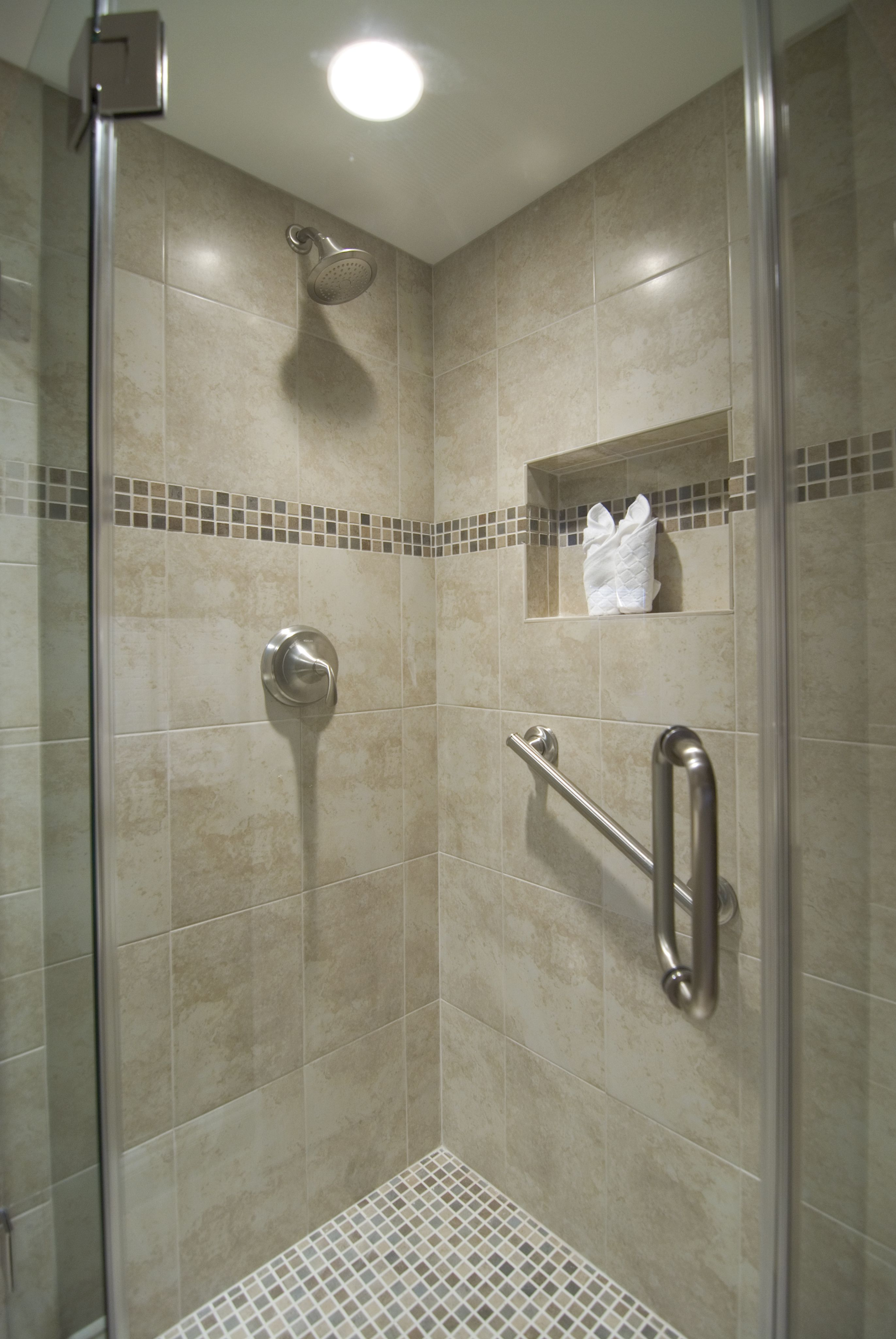 Oliva Oceano Mosaic accents the shower wall tiled in Crema