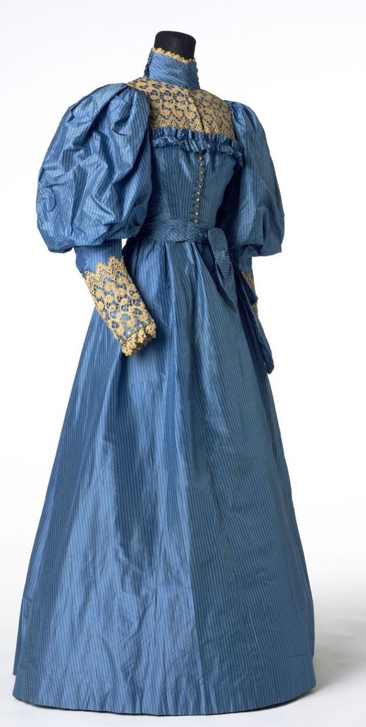 "Wedding Dress: 1894, Welsh, silk, cotton, brass, glass. ""This blue silk wedding dress was worn for a wedding in Wales in 1894. It has leg-of-mutton sleeves, which were very fashionable at the time and reached their largest in the mid 1890s. These enormous puffs had to be balanced by a wide skirt and tight waist, as seen in this dress."""