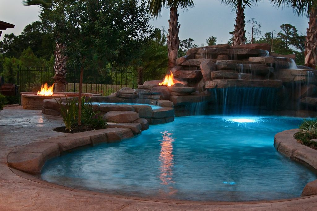 Dramatic Kidney Pool At Night Surrounded By 2 Firepits This Also Has A Cave With Waterfall Entry This Is A Great Swimming Pools Backyard Pool Tropical Pool