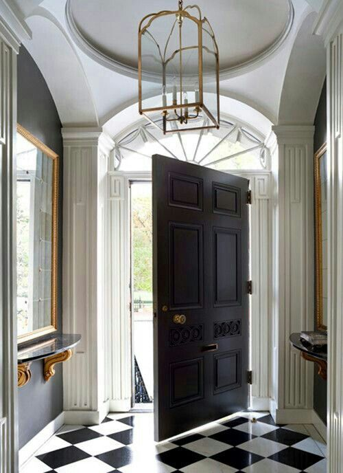 foyer with black door and black and white checked floors Vita