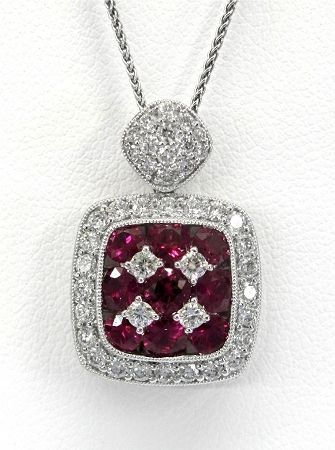 Ladies 18kt white and yellow gold gemstone and diamond pendant. Mounted in pendant are 9 brilliant round cut rubies and 38 brilliant round cut diamonds weighing a total of approximately .69ct. Pendant comes with an 18 inch white gold chain.