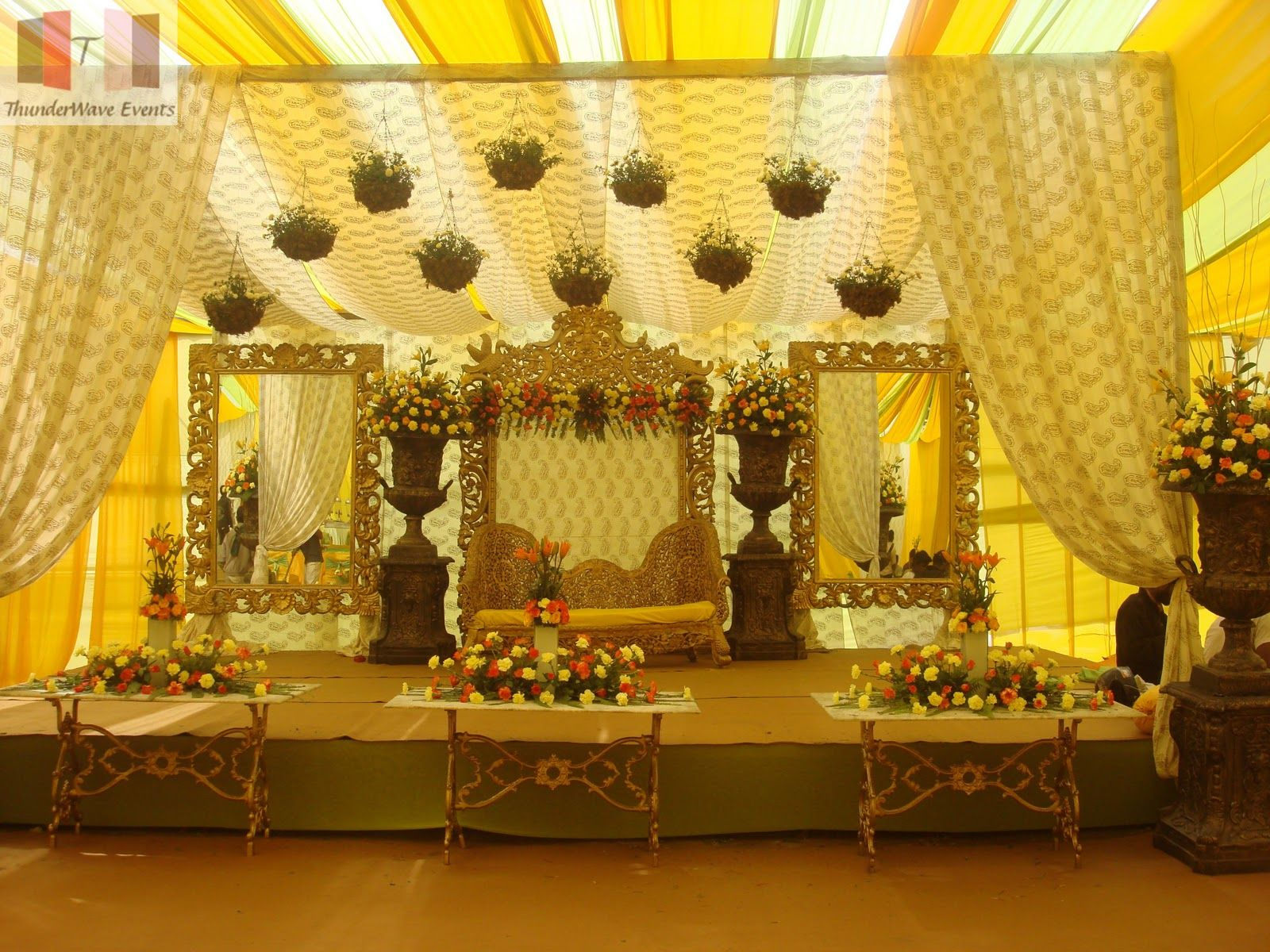 Wedding Stage Decoration Price : A simple stage decor with yellow drapes gold seats and