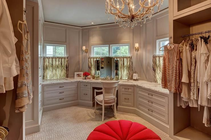 Gray walk-in closet features gray built ins fitted with a make up vanity and a white cane back chair placed under a window dressed in cafe curtains.