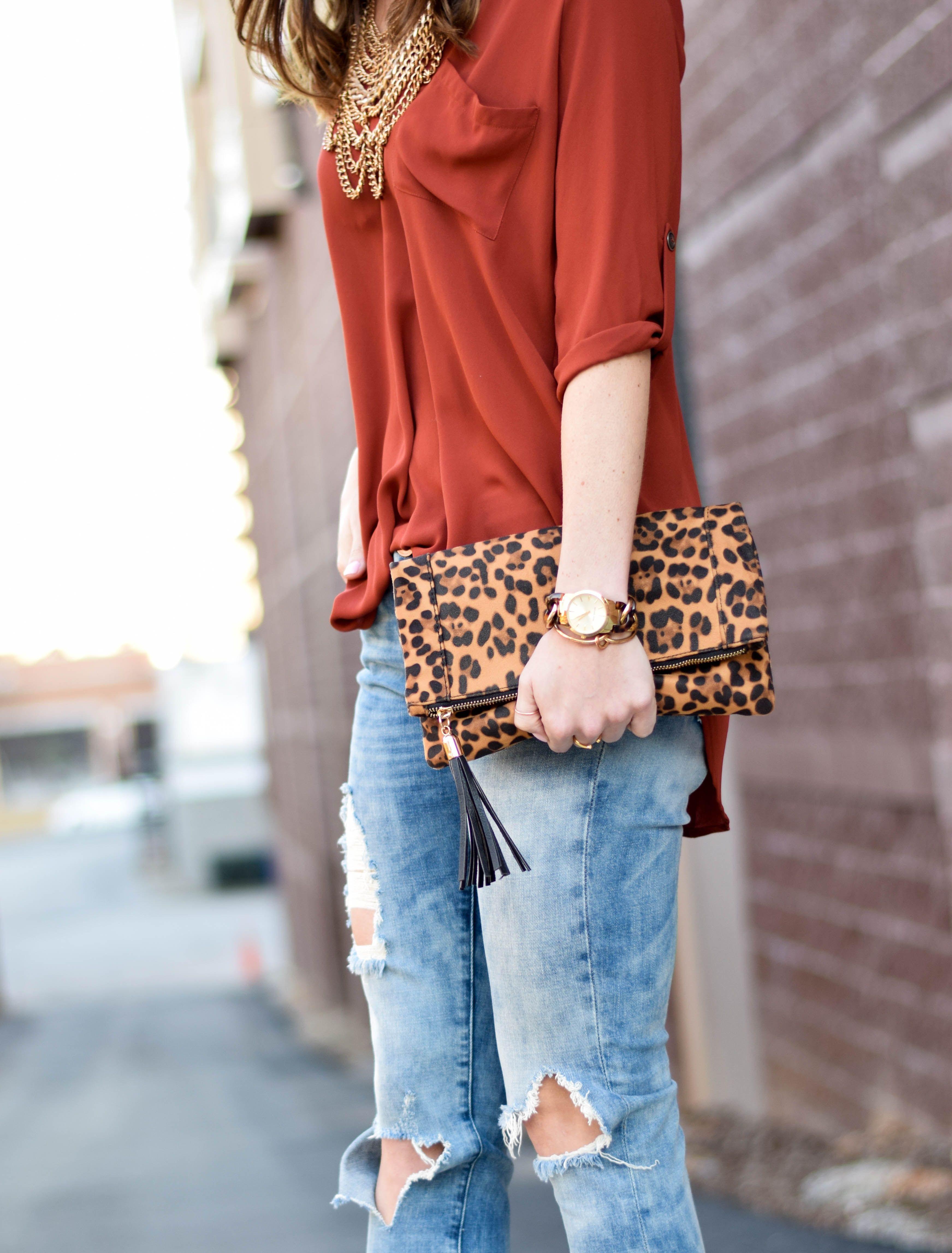 Burnt orange tunic, distressed denim, leopard clutch