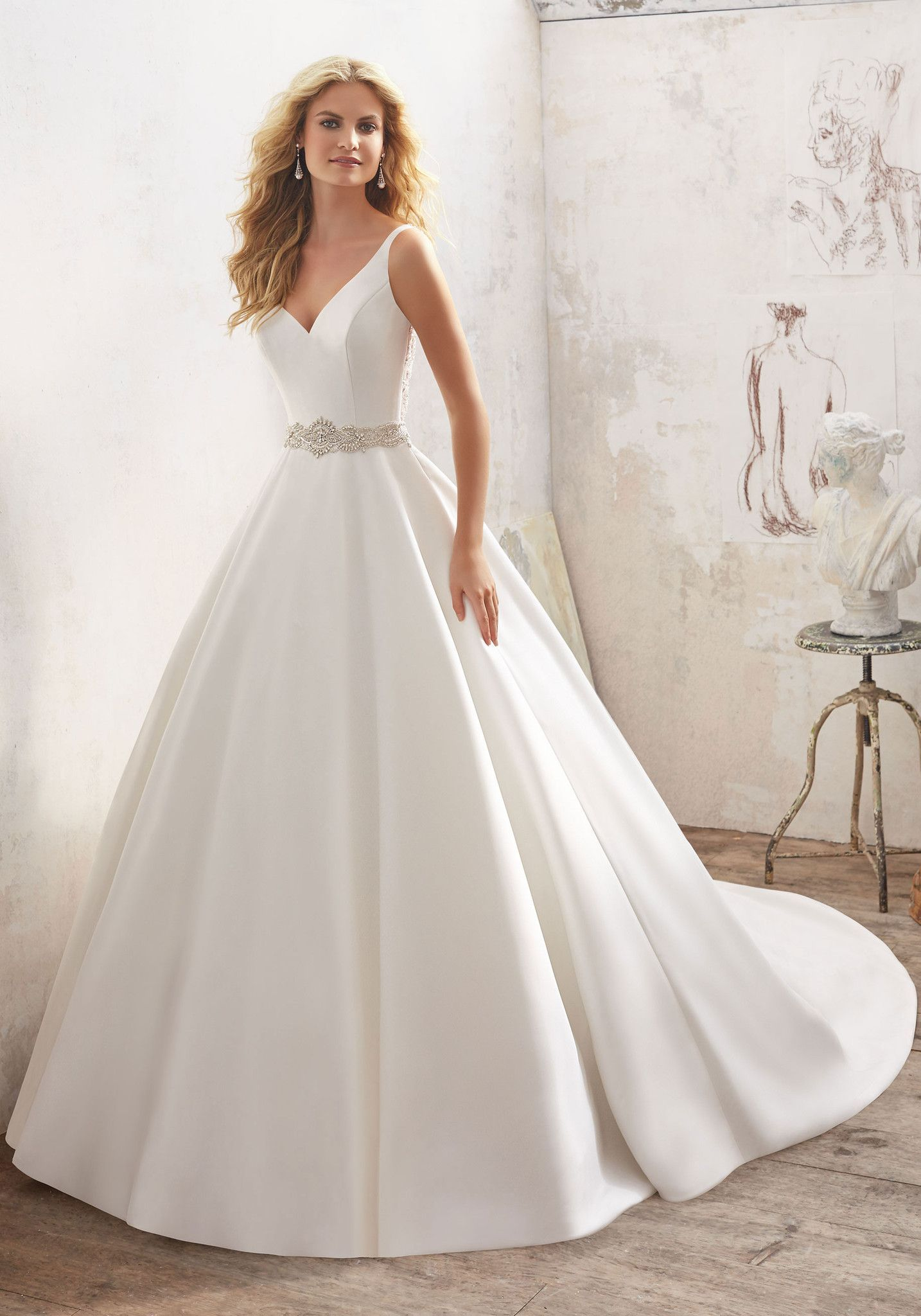 Understated and Elegant, This Stunning Marcella Satin A-Line Bridal Gown Features a Crystal Beaded Sheer Back and Waistline. Covered Buttons Trim the Back and Train. Available in White/Silver, Ivory/S