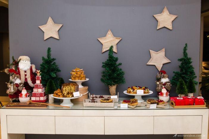mesa de doces feita com pinheiros de natal, pratos de estrelas colados na parede, pratos com doces e panetones temáticos e enfeites de natal como papai noel e árvore de resina.