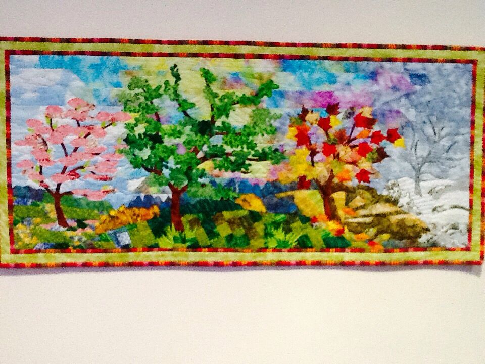 'Trees of the season'. Pieced background and sky, raw edge appliqué trees and leaves