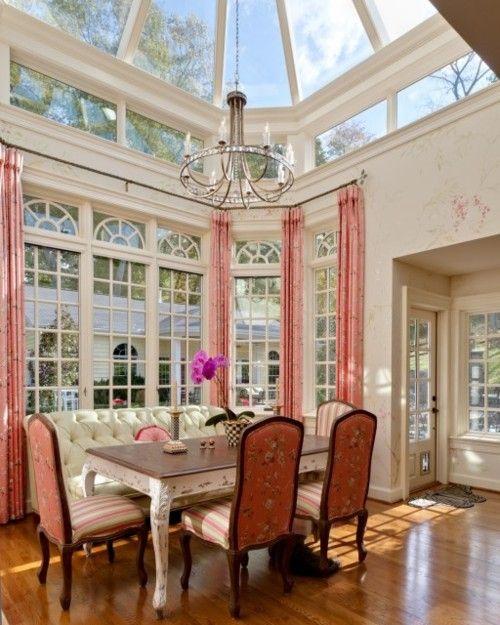 A sensational dining room, with a sofa utilized as a banquette, and a glass atrium ceiling