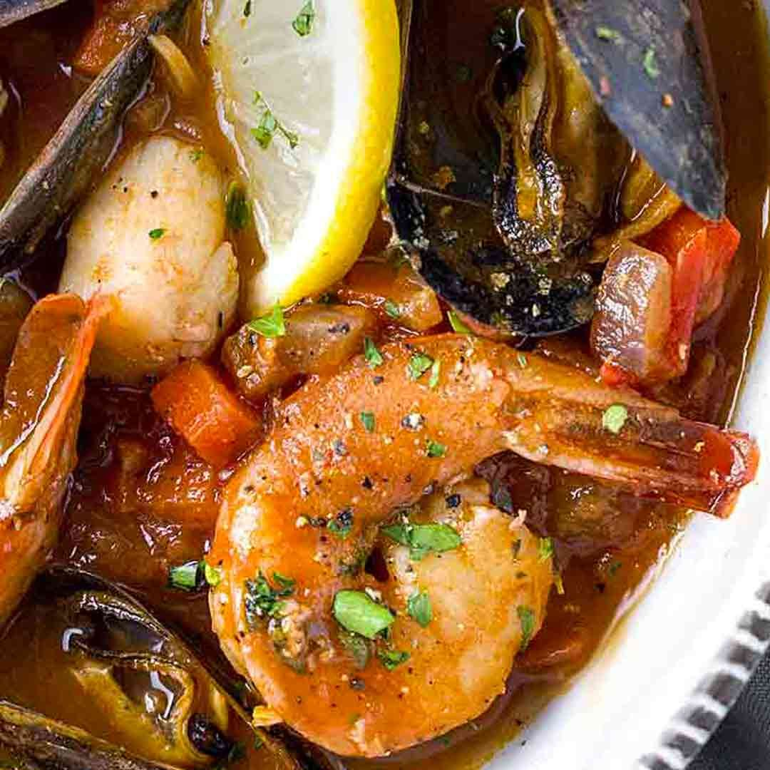 This San Francisco-style seafood cioppino is loaded with fresh mussels, shrimp and scallops simmered in a savory red wine tomato broth for the ultimate one-pot meal! #seafood #video #cioppino #bayareafood #mussels #seafoodstew