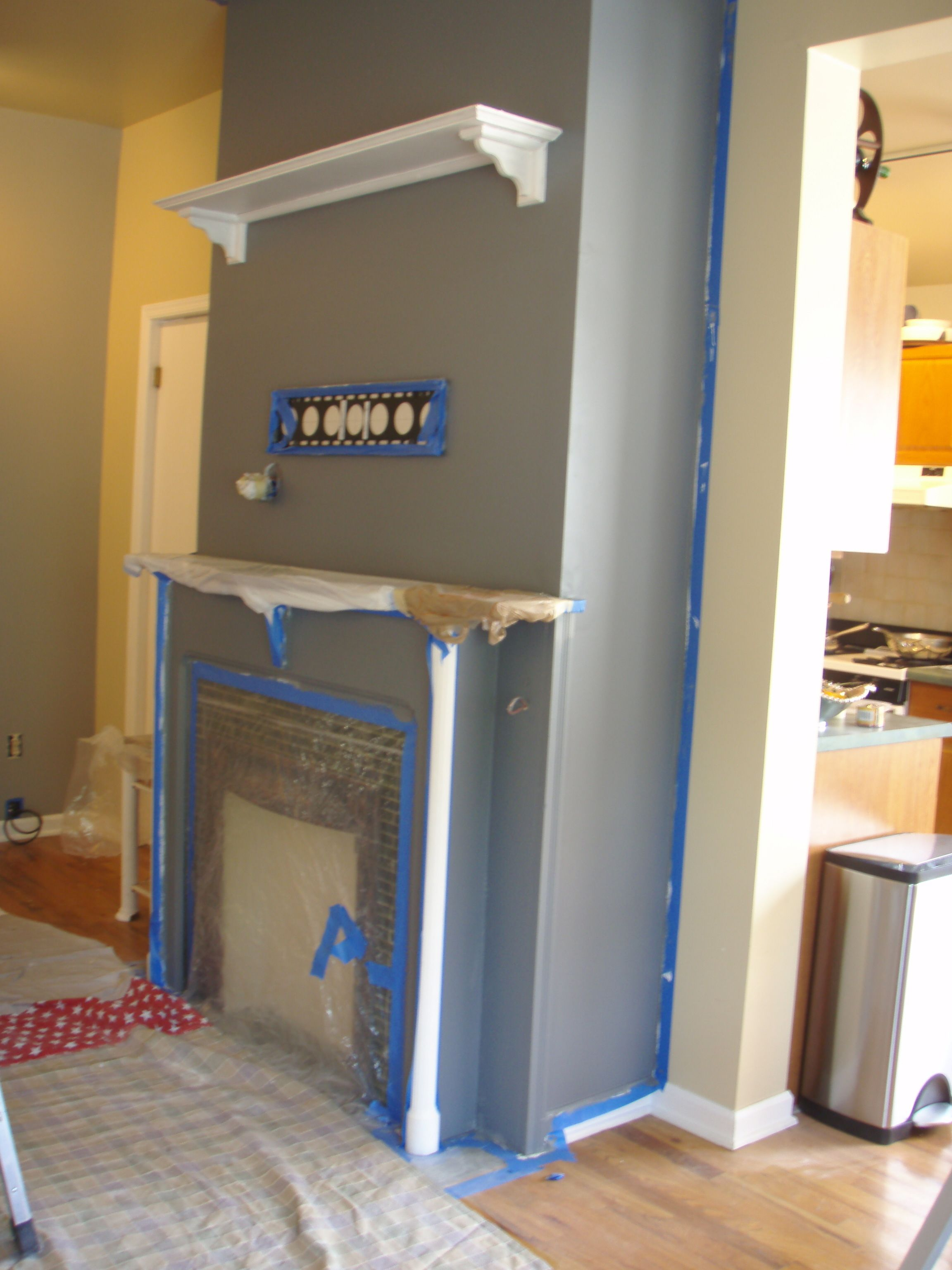 Blue fireplace accent piece with soft yellow wall all around