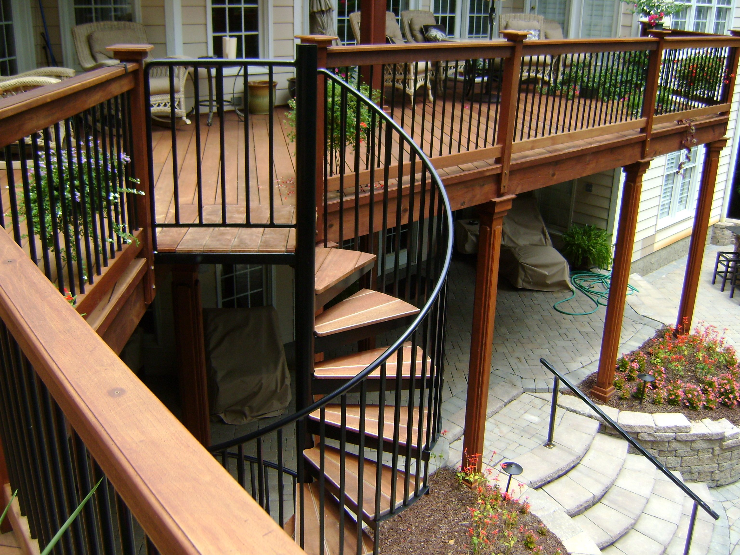 Second Story Wood Deck With Spiral Staircase And Stone Patio
