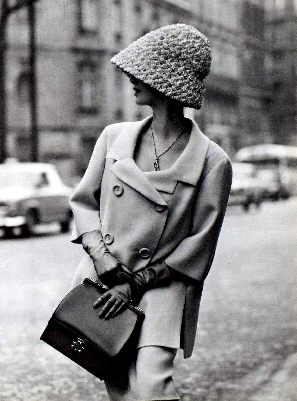 Model in double-breasted Shetland crême wool suit with longer,loose jacket, 3/4 sleeves by Jean Patou, gloves and purse by Hermès, photo by Georges Saad, Paris, 1962
