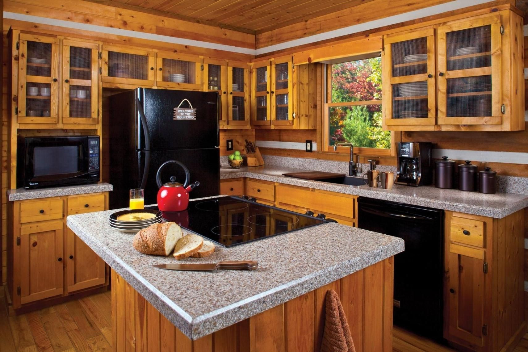 Natural oak wood kitchen cabinets and island installed in small rustic kitchen idea and combined with gray granite countertops and black kitchen appliances