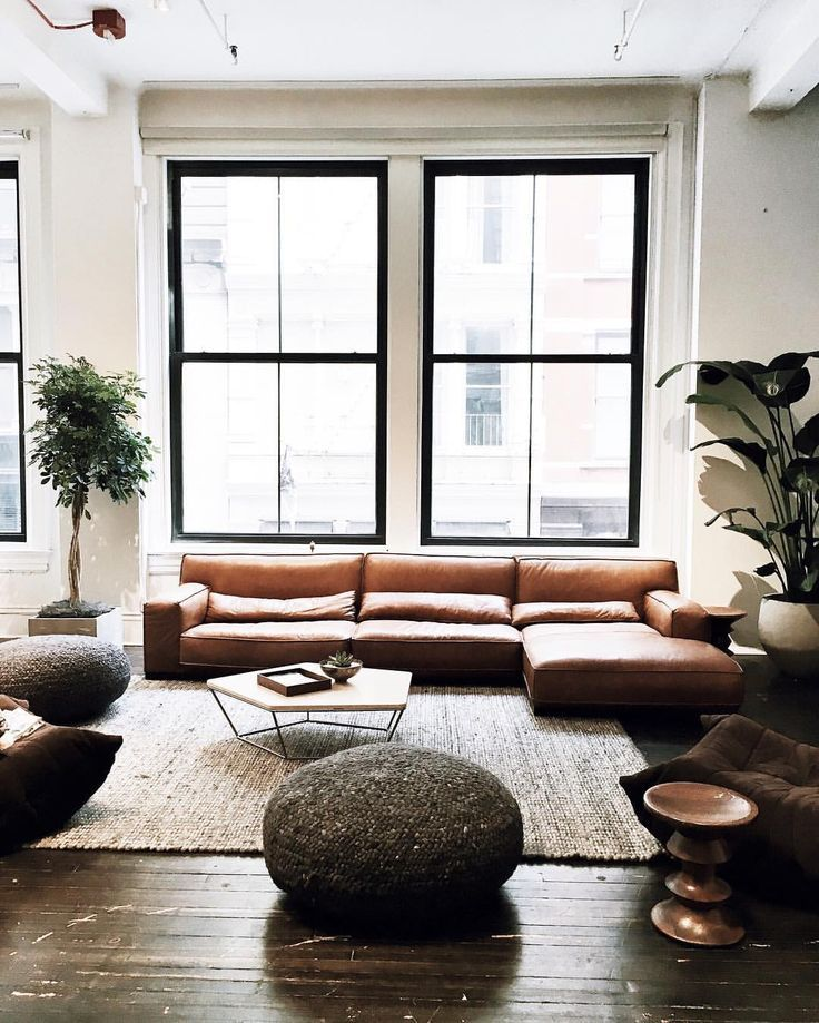 black steel-frame windows, camel leather sofa, jute rug ...