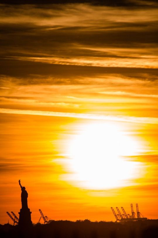 Statue of Liberty at sunset 지지 않는 태양 석양 형태를 띠고 빛을 내게 해서 야간에도 지지 않고 떠있는 태양을 형상화