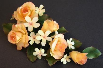 Here is a spray of gumpaste tea roses and blossoms along with rose leaves.