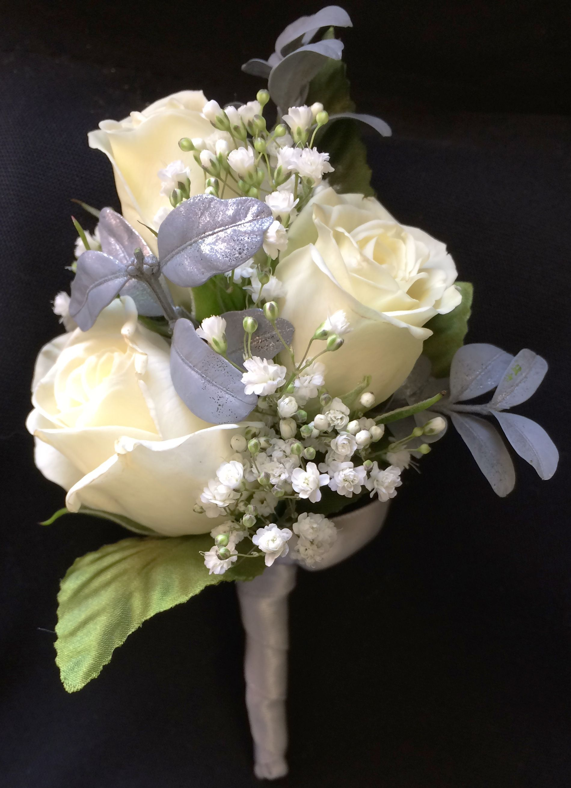 Radiance boutonniere by Kar-Fre Flowers features white spray roses accented by babies breath and silvery gray foliage and is stem wrapped in a creamy white to match the roses.