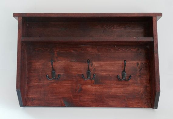 This wall mounted coat hanger provides a perfect place to hang your jackets, scarves, purse or keys, while providing a cubby space above for other odds and ends! The stained wood and the black 3-pronged hooks have a neutral finish that pairs nicely with a variety of colors and decor. This piece is sure to look wonderful in any wall of your home!