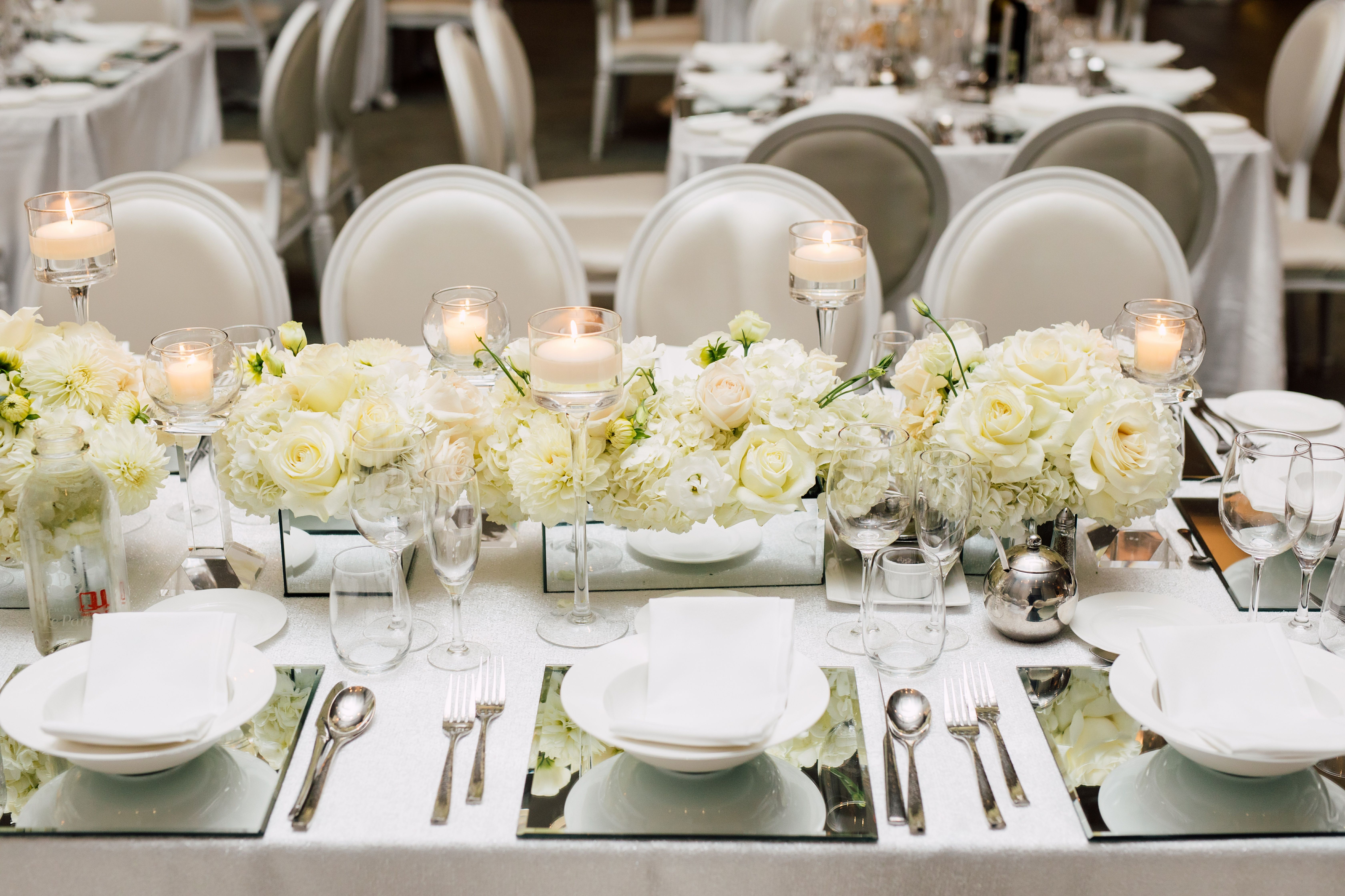 All white floral centerpiece with dahlias, hydrangea and roses. In a ...