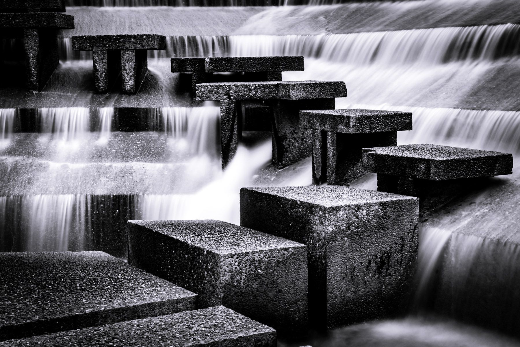 Water cascades around concrete steps at the Fort Worth