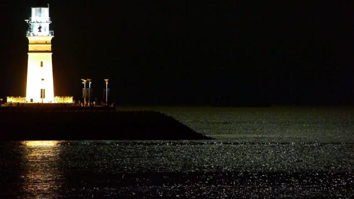 Lighthouse at night,moon light reflect on sea.