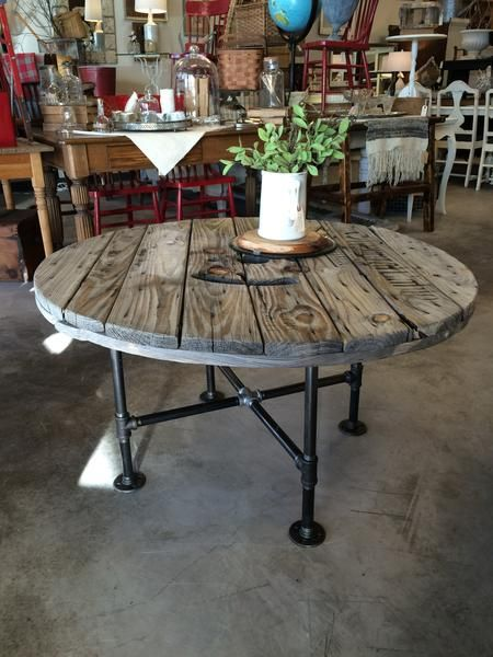Industrial table made of black steel pipe and a reclaimed Southwire cable spool. 40 diameter 20 high. Shown with crossmember-style base with feet, black steel pipe. #cablespooltables