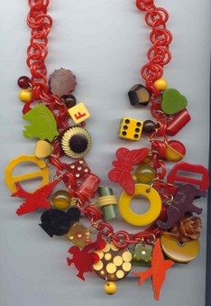 Bakelite charm necklace, Bakelite is very collectable, it looks a lot like plastic, but has a different surface feel, heaver, has a color different than plastic, whites tinge yellow, and yellow a mustard color.  All kinds of things where made from Bakelite not just buttons.