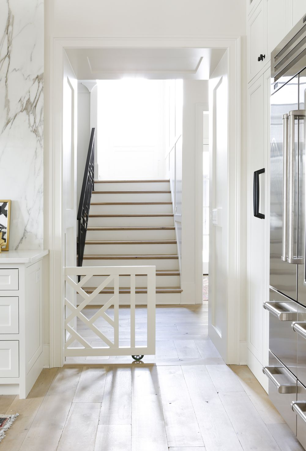 A White Lattice Safety Gate Opens To A Kitchen Clad In Rustic Wood Plank  Floors.