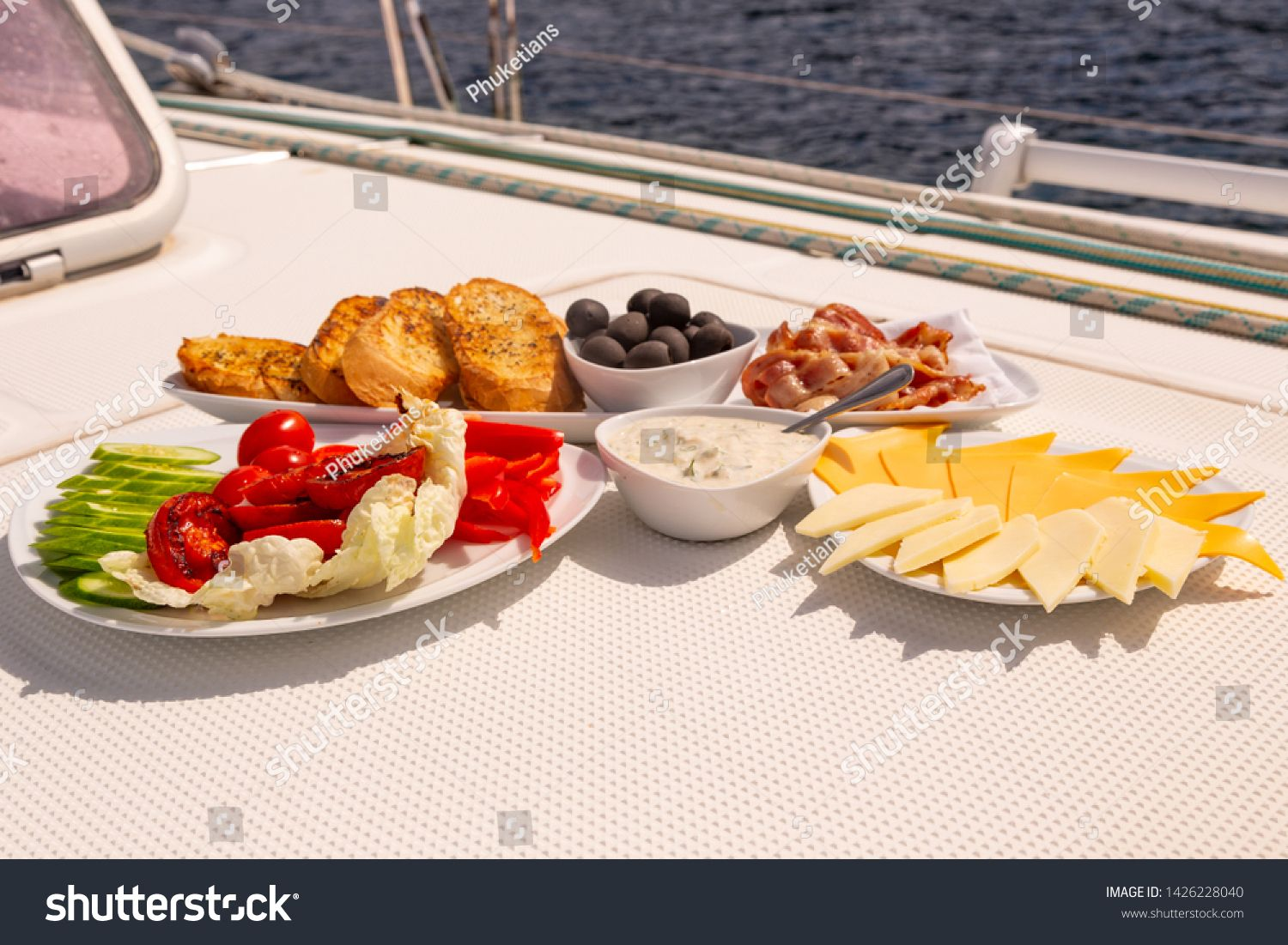 American breakfast on sailing yacht. Luxury holiday meal at the sea on the yacht. Bacon, omelette,