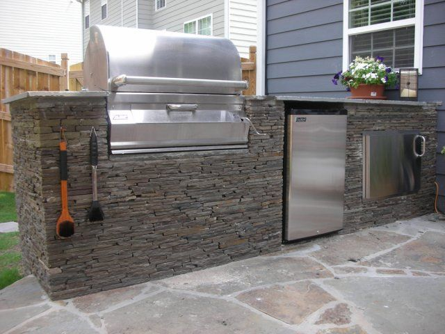 Outdoor Kitchen With Sacked Stone, Drop-in Grill, Refrigerator And An Ice Box? Love The Cooler