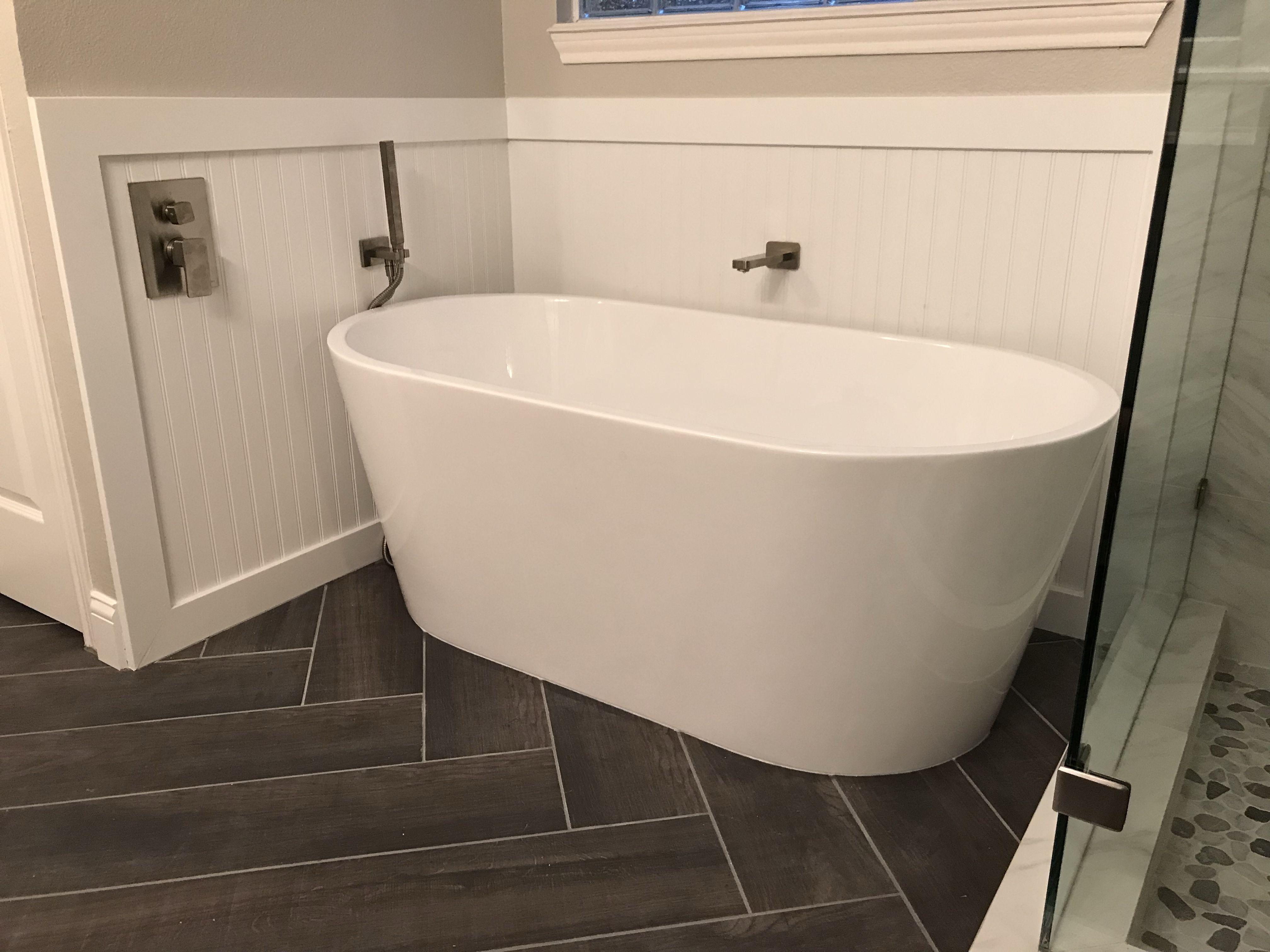 Free Standing Tub On Herringbone Wood Tile Plank Floor With