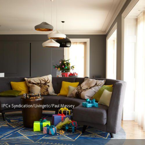 Zu dem dunklen Grau dieses Wohnzimmers setzen die bunten Kissen farbenfrohe Akzente. Die Rentiermotive und der kleine Weihnachtsbaum sorgen für eine festliche…