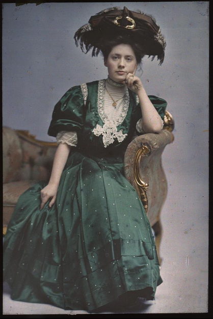 Woman in Green Dress. 1908. Autochrome portrait of woman seated on a couch, in a green dress with feathered hat. DESCRIPTION William H. Towles, active from 1890 into the 1930s, is said to have made Washington, D.C.'s first autochrome. Autochromes are among the first commercially successful forms of color photography. The color dyes in the photographs are held by potato starch.
