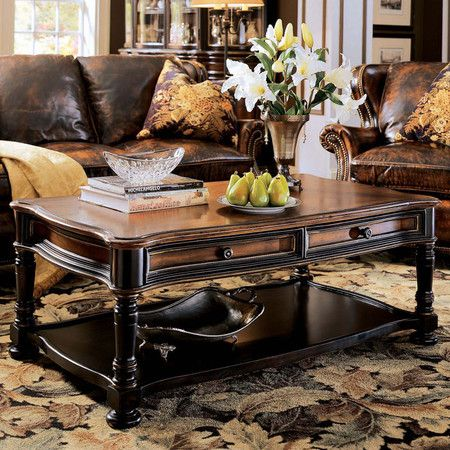 Distressed hardwood coffee table with two drawers and an open display shelf. Finished in contrasting cherry and black rub-through.  ...