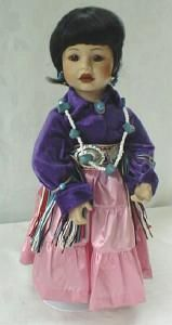 Offering this Ray Swanson porcelain American Indian doll called  Dressed Up For The Pow Wow . She is 15 1/2  tall, dressed in purple velour velvet blouse and bright pink satin skirt, adorned with a white beaded & faux turquoise necklace, a silver metal conches on colorful woven cloth belt with multi strand ties on sides. A white multi strand hair bow ties her hair in back which is in traditional Navaho style. She is also wearing a faux turquoise brooch and earrings. White cotton pantaloons…