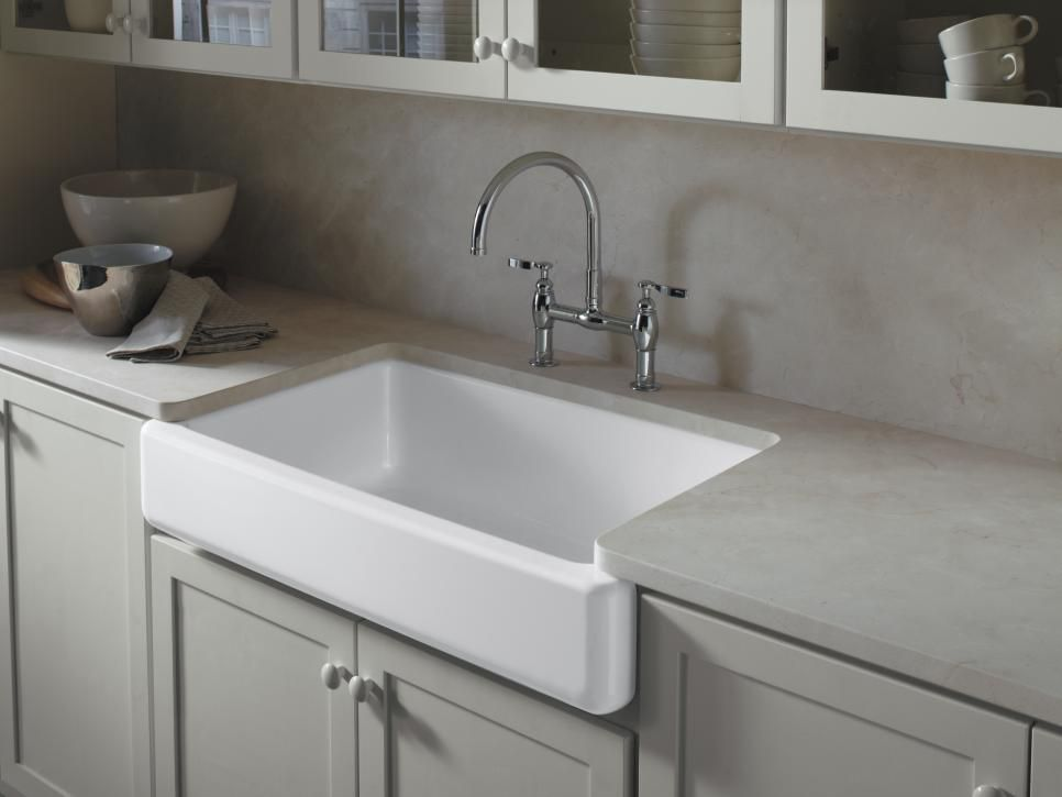 """Kohler's apron-front cast-iron sinks come in a variety of colors, including new neutral tones Dune, a soft sandy shade, and Suede, a dark hue that pairs well with granite countertops. """"Apron-front sinks have never gone out of style,"""" says interior designer Christine Baumann. """"They add a timeless focal point to any kitchen. From a practical standpoint, they're deep enough to hold large pots and platters for easier cleanup — a shorter person can even benefit from better access to the sink.""""…"""