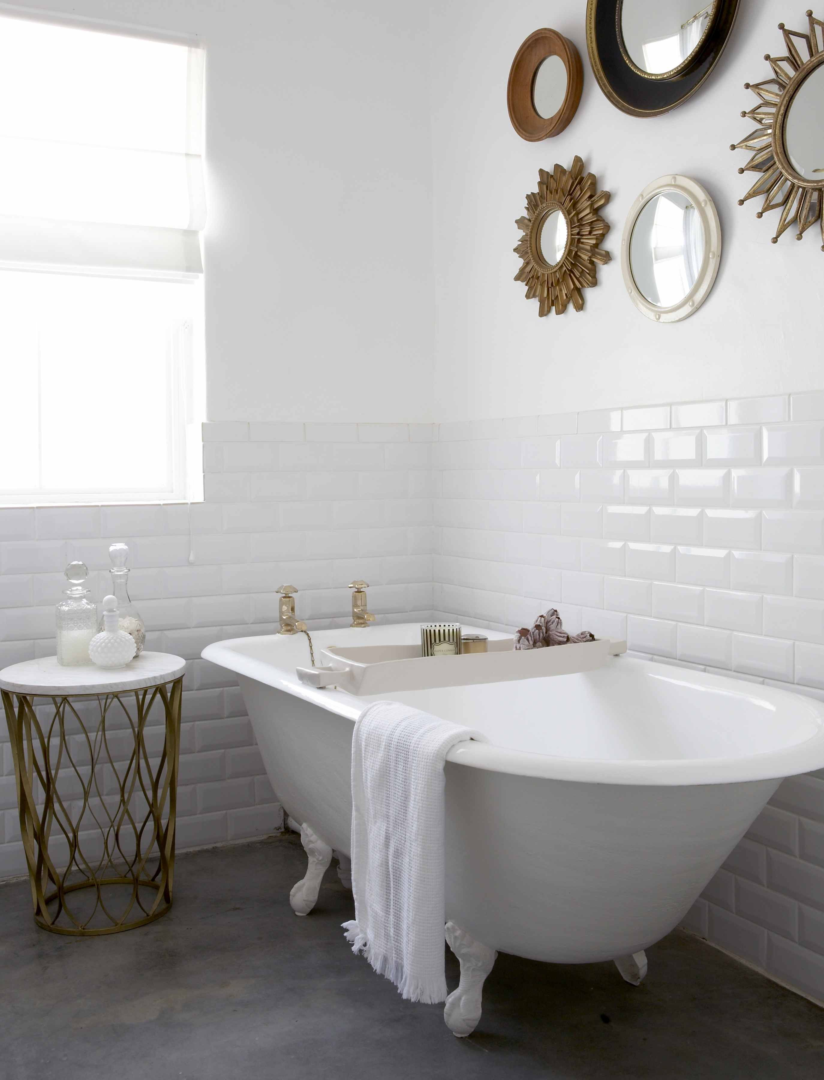 Bathroom with ball-and-claw bath. Collection of circular mirrors ...