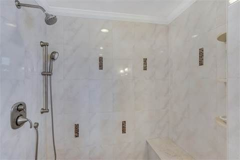 A Luxurious Shower Stall With Marble Tiles And Crown Molding In This Home  In Belmar,