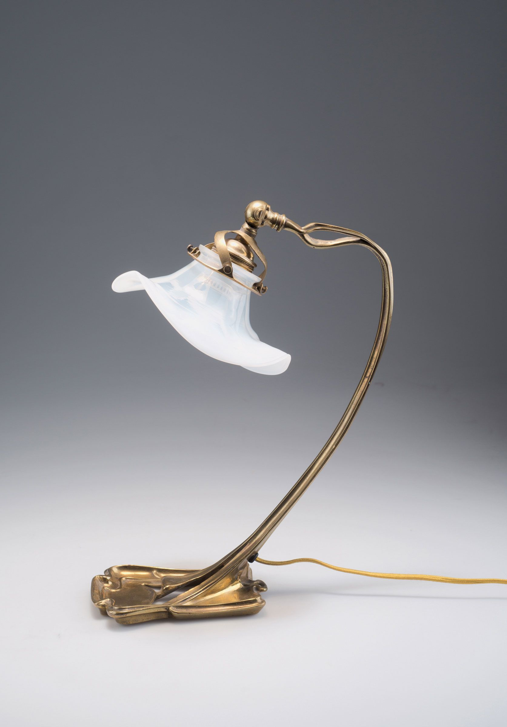 Munich. Table light, c1900. H. 34 cm. Shade designed by Richard Riemerschmid. Cased glass, clear and milky white. Brass base. Electrified.