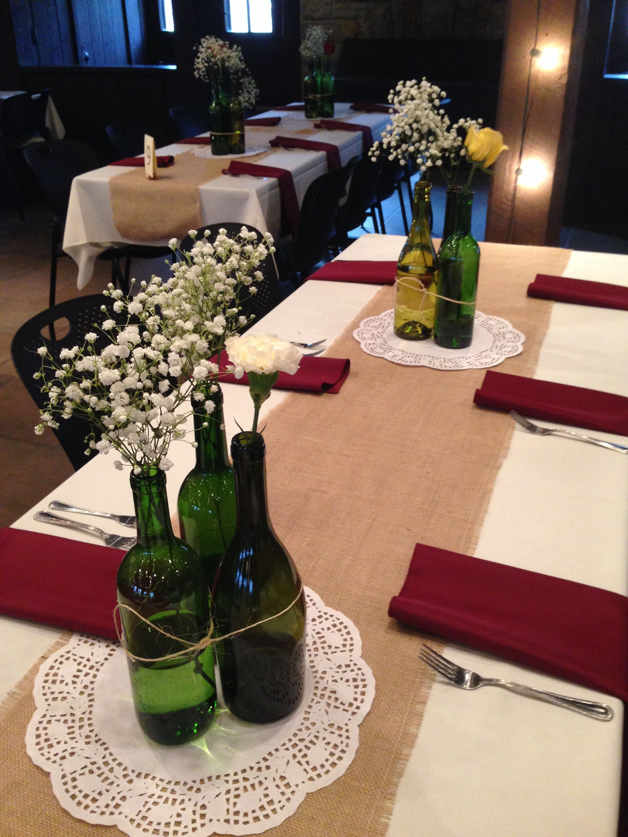 Burlap table runners, roses, carnations, and baby's breath in recycled wine  bottles.