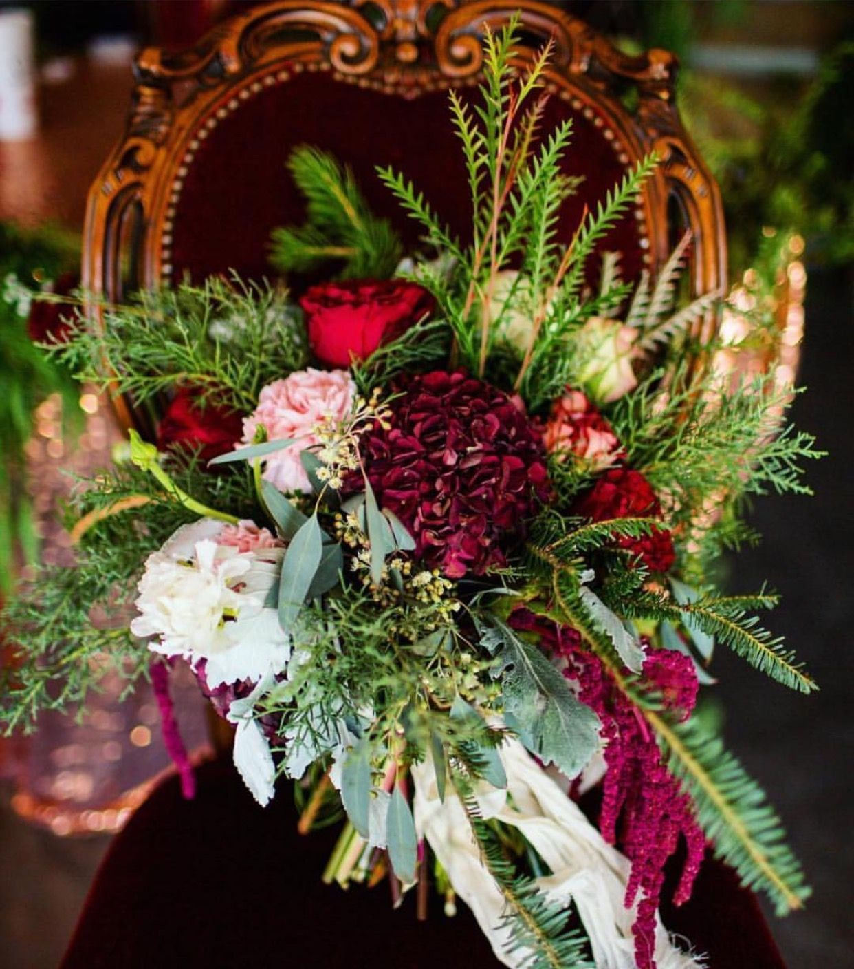 Darling Bouquet filled with curly pine, hanging amaranthus, cedar,cypres,pine, dusty miller, garden roses, carnations, hydrangeas, spray roses, & seeded eucalyptus! And of course our Crushed Vintage Red Velvet Chair is a stunning accessory !