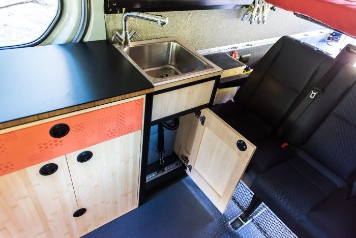 Sink cabinet with grey water tank strapped in underneath Sprinter
