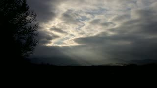 Stock Footage | Timelapse of clouds in the hills with the sun's rays | Download using the VidLib app. 50.000 Royalty Free Clips'