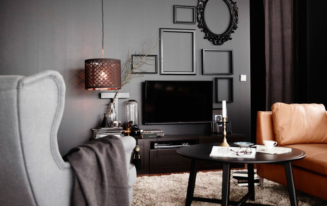 One way to hide your TV is to paint the wall behind black and decorate with black frames for a distinctive style expression