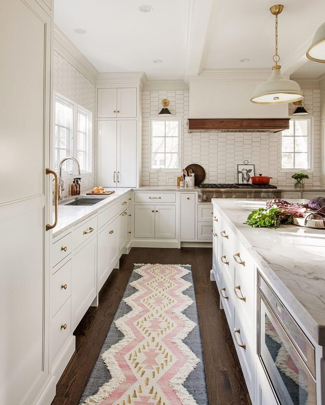 White kitchen with tile backsplash and blue and pink runner rug ...