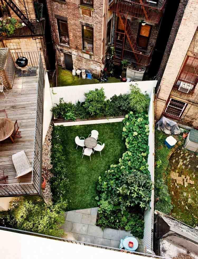 terrasse de jardin en ville, gazon, dalles de pierre et végétation copieuse