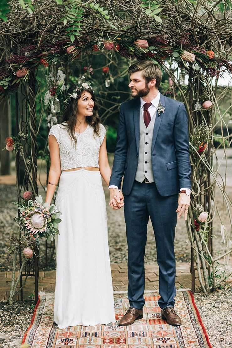Rustic Boho Bride And Groom In Front Of Australian Native Flower Ceremony Arbour