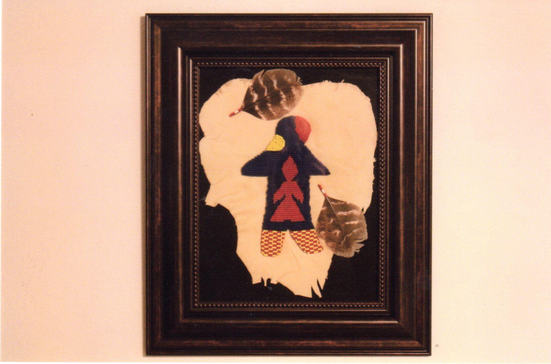Hand beaded bear figure on leather, with wild turkey feather decoration -- framed. Karen. A. Holt, artist